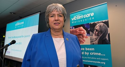 Jane Kennedy in front of a Victim Care Merseyside banner